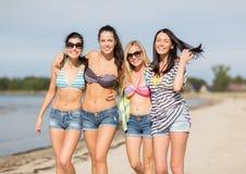 Flickor i bikinier som går på stranden Royaltyfri Bild