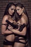 Flickor i damunderkläder med skjutvapen Royaltyfri Bild