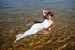 Flickor i den vita klänningen som ligger i vatten Arkivfoto
