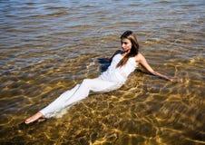 Flickor i den vita klänningen som ligger i vatten Fotografering för Bildbyråer