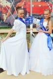 Flickor i härliga vita klänningar poserar på nätter för festivalen för öppen luft vita Royaltyfri Fotografi