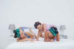 Flickor i hårrullar som har gyckel i säng Arkivfoton