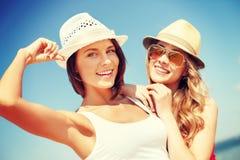 Flickor i hattar på stranden Arkivbilder