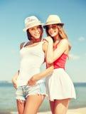 Flickor i hattar på stranden Royaltyfri Bild