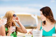 Flickor i kafé på stranden Royaltyfria Bilder