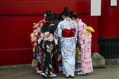 Flickor i kimanoklänningar står nära väggen i Senso-ji tempelAsakusa område, Tokyo, Japan royaltyfria bilder