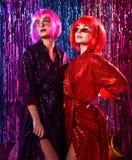 Flickor i peruker och stilfulla glamor?sa kl?nningar med paljetter, i neonljuset av ett disko Fira, ha gyckel, fira n?got royaltyfria bilder