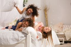 Flickor i säng som har kuddekamp i pyjamas arkivbilder