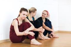 Flickor i sportswearsammanträde på golvet nära väggen som den har, vilar efter konditionutbildning Gruppen av barn passade att si royaltyfria foton
