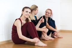 Flickor i sportswearsammanträde på golvet nära väggen som den har, vilar efter konditionutbildning Gruppen av barn passade att si arkivfoto