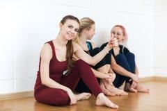 Flickor i sportswearsammanträde på golvet nära väggen som den har, vilar, efter konditionutbildning har visat tummen och har lett royaltyfri bild