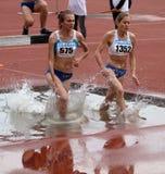 Flickor konkurrerar i den 3.000 räkneverk steeplechasen Royaltyfria Foton