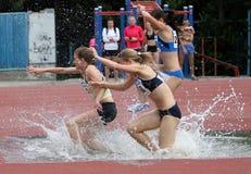 Flickor konkurrerar i den 3.000 räkneverk steeplechasen Arkivbild