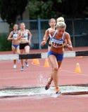 Flickor konkurrerar i den 3.000 räkneverk steeplechasen Arkivfoto