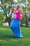Flickor konkurrerar i en stafett Hoppa i påsar De skrattar och faller Arkivfoton