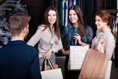 Flickor konsulterar med shoppar assistenten arkivbild