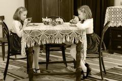 Flickor kopplar samman att dricka te på en antik tabell med en snöra åttablecl Arkivfoto