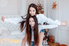 Flickor kopplar samman framme av gran-trädet Helgdagsafton för ` s för nytt år Jul Hemtrevlig ferie på gran-trädet med ljus royaltyfria bilder