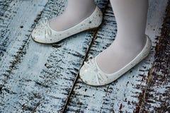 Flickor lägger benen på ryggen med vita sockor i vita häftklammermatare Royaltyfri Bild