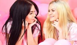Flickor lägger på ballonger för buken nära, rosa bakgrund Skvallerbegrepp Systrar eller bästa vän i pyjamas på flickaktig pyjamas Arkivbild