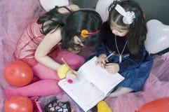 flickor little writing Fotografering för Bildbyråer