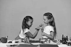 Flickor med att le vänder mot vid deras konstskrivbord med brevpapper Fotografering för Bildbyråer