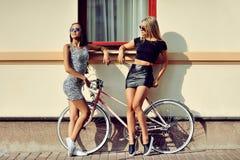Flickor med cykeln utomhus- stående för mode Fotografering för Bildbyråer