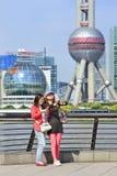 Flickor med den smarta telefonen gör selfie med Pudong på bakgrund, Shanghai, Kina Fotografering för Bildbyråer