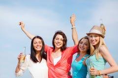 Flickor med drinkar på stranden Arkivbild