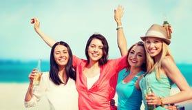 Flickor med drinkar på stranden Arkivfoto