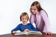 Flickor med en bok på en vit bakgrund Arkivbilder