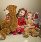 Flickor med jul- och björngåvor royaltyfria bilder