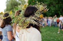 Flickor med kransar av lösa blommor kör rund dans Royaltyfri Bild
