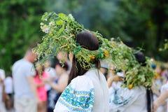Flickor med kransar av lösa blommor kör rund dans Arkivbild
