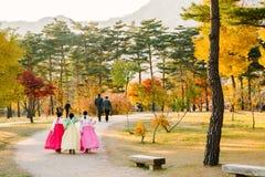 Flickor med lönnlöv för Hanboktraditional koreanska klänning- och gulinghöst i den Gyeongbokgung slotten Royaltyfri Foto