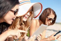 Flickor med minnestavlaPC på stranden Arkivfoton
