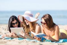 Flickor med minnestavlaPC på stranden Arkivbilder