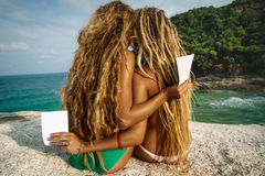 Flickor med reklamblad på stranden Royaltyfri Bild
