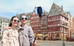 Flickor med smartphoneselfiepinnen i frankfurterkorv Royaltyfri Fotografi