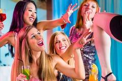 Flickor med utsmyckade coctailar i remsaklubba Royaltyfri Bild