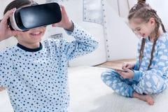 Flickor med virtuell verklighethörlurar med mikrofon och digitalt minnestavlasammanträde på matta Arkivbilder
