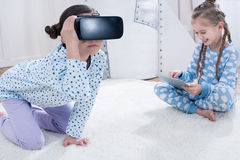 Flickor med virtuell verklighethörlurar med mikrofon och digitalt minnestavlasammanträde på matta arkivfoto