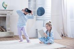 Flickor med virtuell verklighethörlurar med mikrofon och digitalt minnestavlasammanträde på matta Arkivbild