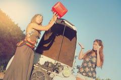 Flickor nära en bil med inget bränsle Fotografering för Bildbyråer