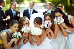 Flickor och bruden poserar med bröllopbuketter medan brudgummen och brudgummen Royaltyfri Fotografi