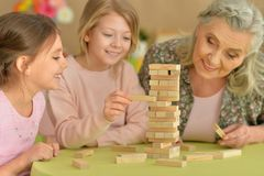 Flickor och farmor som spelar med kvarter Fotografering för Bildbyråer
