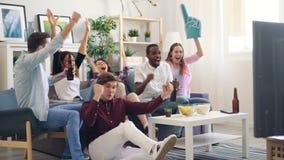 Flickor och grabbar som tillsammans hurrar och kramar hållande ögonen på sportar på TV i lägenhet lager videofilmer