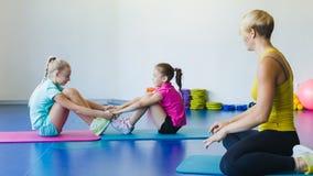 Flickor och instruktör eller moder som gör gymnastiska övningar i konditiongrupp arkivfilmer