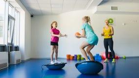 Flickor och instruktör eller moder som gör gymnastiska övningar i konditiongrupp stock video