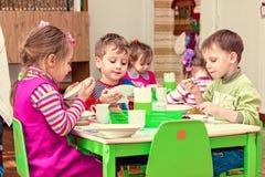 Flickor och pojkar äter på tabellen Arkivbild